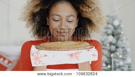 Young African woman with a freshly baked Christmas tart held in her hands smiling in pleasure as she savors the aroma