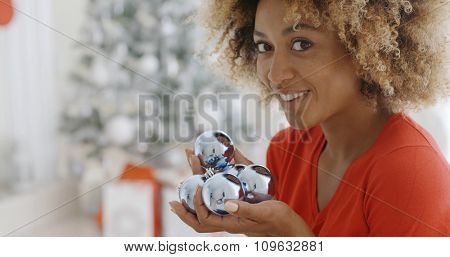 Young woman carrying a handful of Xmas decorations looking at the camera with a happy friendly smile as she prepares to add them to the ornaments on the Christmas tree in her living room.
