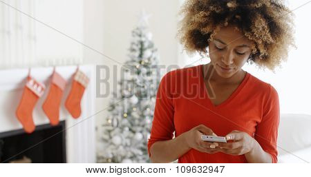 Attractive young African woman checking her Christmas messages on her mobile phone with a smile as she stands in her decorated living room