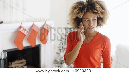 Trendy young African American woman chatting on her mobile phone at Christmas standing in a decorated living room  close up upper body portrait