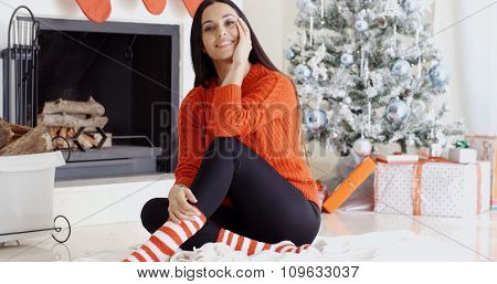 Trendy gorgeous young woman relaxing at Xmas sitting on a rug on the floor in front of the Christmas tree grinning at the camera