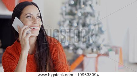 Pretty young woman chatting on her mobile phone in her living room in front of the Christmas tree looking at the camera with a beaming smile.