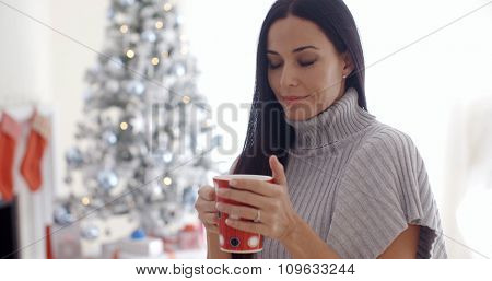 Attractive young woman enjoying a cup of Christmas coffee in front of the decorated tree