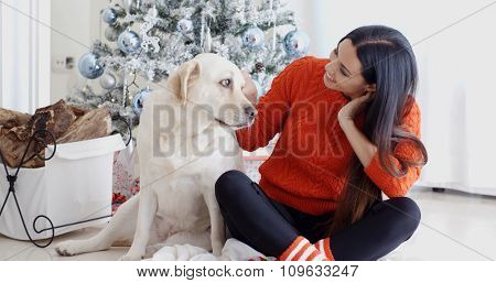 Young woman and her golden labrador dog celebrating Christmas together sitting on the floor in fornt of the decorated tree