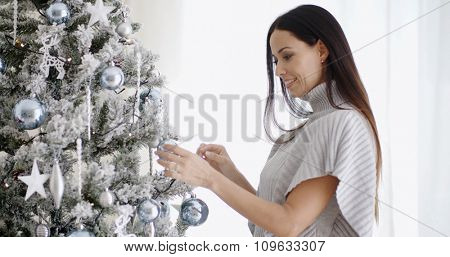Pretty trendy woman decorating an Xmas tree placing traditional Christmas ornaments and tinsel on the branches with a happy smile