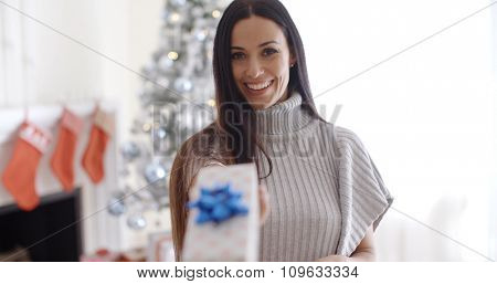 Smiling pretty young woman standing in front of the Xmas tree holding out a decorative Christmas gift towards the camera