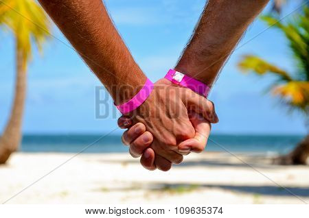 Happy gay couple on the beach holding hands