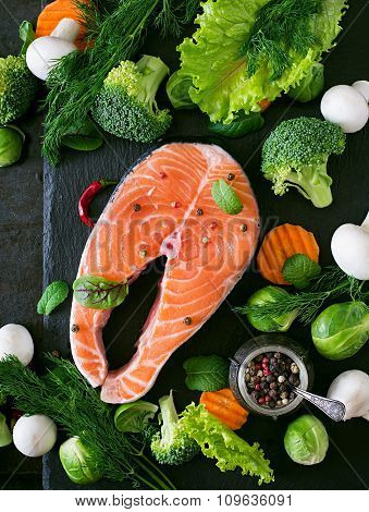 Raw salmon steak and ingredients for cooking on a dark background in a rustic style.