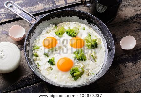 The frying pan with fried eggs with broccoli