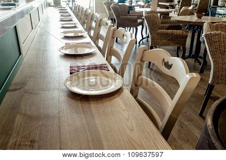 long wooden table decorated with dishware for banquet
