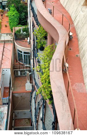 BARCELONA, SPAIN - MAY 01: High Angle View Looking Down at Walkway Along Exterior of Casa Mila Wall with Green Potted Plants and Balconies, Barcelona, Spain. May 01, 2015