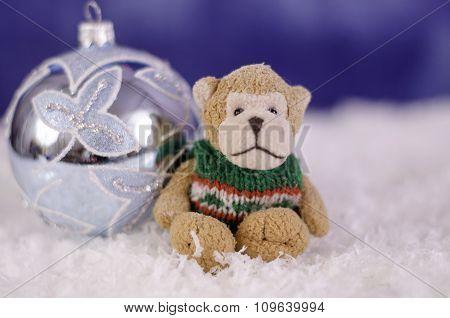 Toy Monkey Near Christmas Toy Ball Close Up.