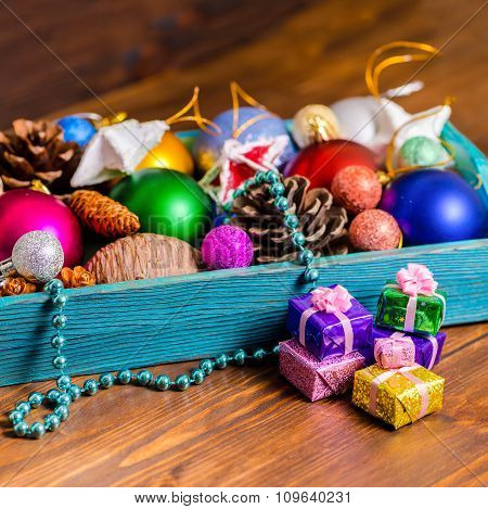 Vintage Wooden Box With Christmas Decoration, Tinsel,  Pinecones, Stars, Balls And Gifts On Wooden B