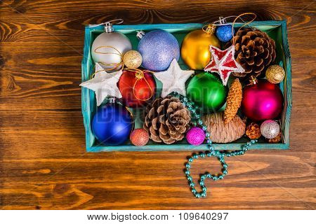Top View Of Vintage Wooden Box With Christmas Decoration, Tinsel,  Pinecones, Stars And Balls On Woo