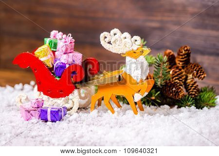 Composition Of Christmas Decoration Reindeer And Santa Sleigh With Gifts, Branch Fir Tree, Pinecones