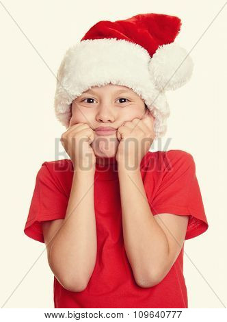 winter holiday christmas concept - boy in santa hat portrait on white isolated