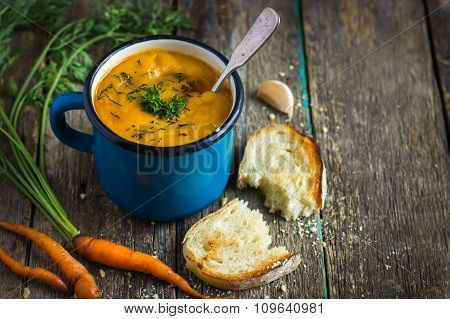 Carrot  Soup In Blue Mug On Rustic Background