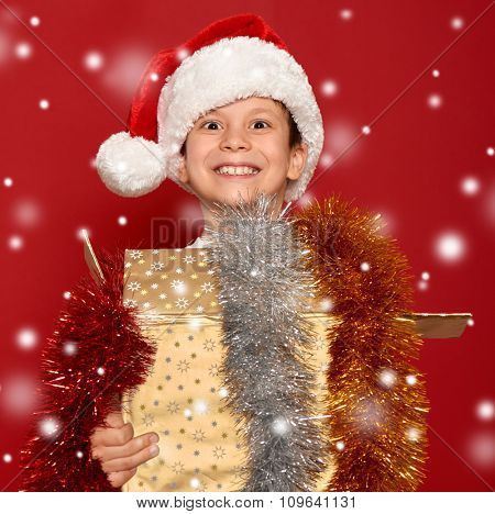 winter holiday christmas concept - boy in santa hat with golden gift box on red background