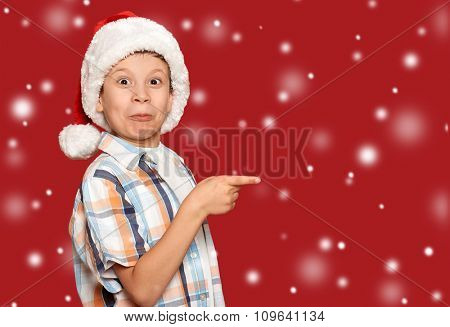winter holiday christmas concept - boy in santa hat point his finger on red background