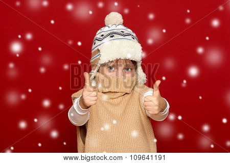 winter, child,  concept - happy girl in hat and sweater show best gesture on red background