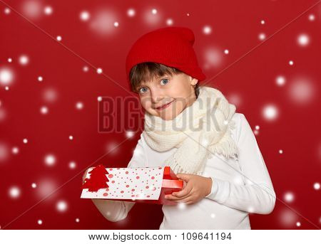 winter, child,  christmas concept - happy girl in hat with box gift show fir tree wool toy on red background