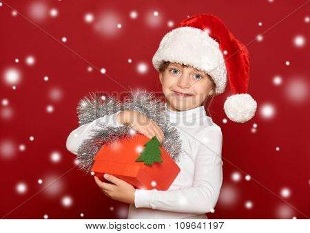 winter, child,  christmas concept - happy girl in santa hat with box gift show fir tree toy on red background