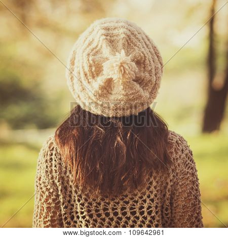 Woman in beige knitted hat and sweater in autumn. Rear view