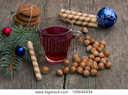 Coniferous Branch With Christmas Tree Decorations, Tea, Sweets And Nutlets
