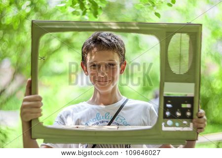 boy playing and looks out of the old TV
