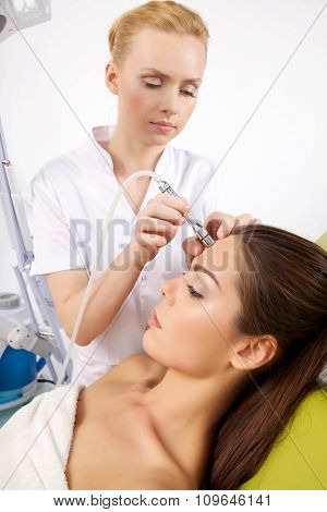 Close up portrait of attractive beautiful sexy and sensuality young adult pretty brunette woman having a stimulating facial treatment from a therapist on the table in professional clinic spa