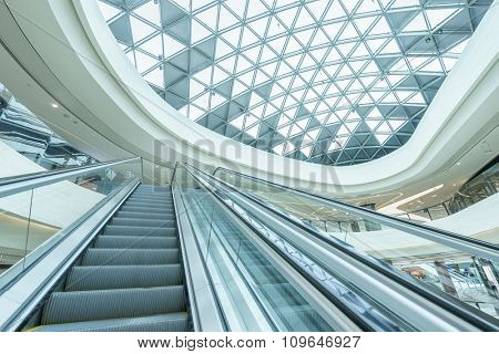 abstract ceiling and escalator in hall of shopping mall
