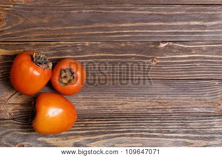 Three Persimmons Isolated On Wooden Background