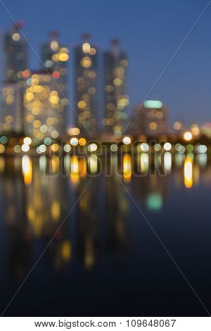 Blurred bokeh lights city downtown background with water reflection