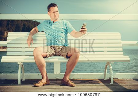 Man Tourist On Pier Using Smartphone. Technology.