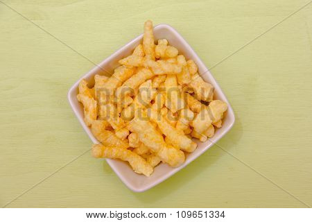 Snack corn cheese in square bowl on green top