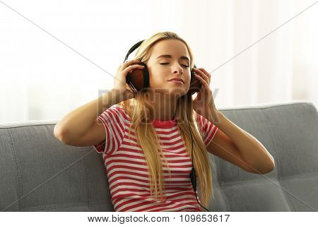 Young woman sitting and listening to music in a room