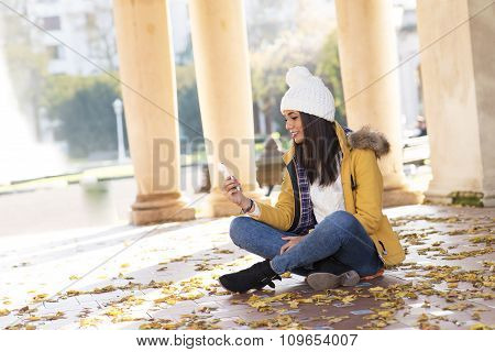 Beautiful Smiling Womanwith Phone Sitting On Leaves.