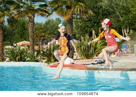 Vacation. little fun children girl and boy jumping into swimming pool