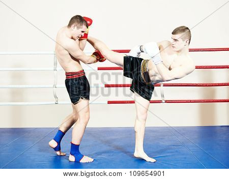 Two male muay thai boxers fighting at training boxing ring