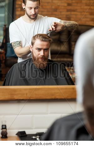 Skillful male hairdresser is serving his client