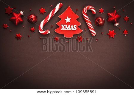 Christmas candy and decorations on brown background