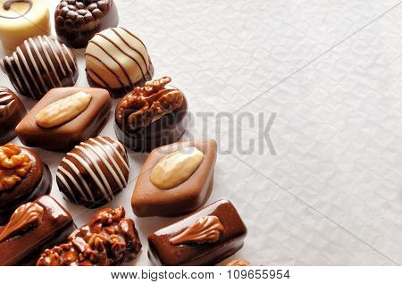 Assorted Bonbons On A White Textured Paper Top View Close-up