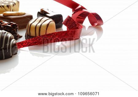 Assorted Bonbons With Red Ribbon On A White Table Front