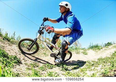 Extreme sport concept. Young cyclist riding the mountain bike uphill or cross-country course