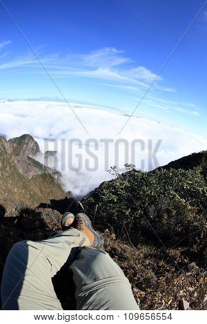 young woman hiker legs sit on beautiful mountain peak