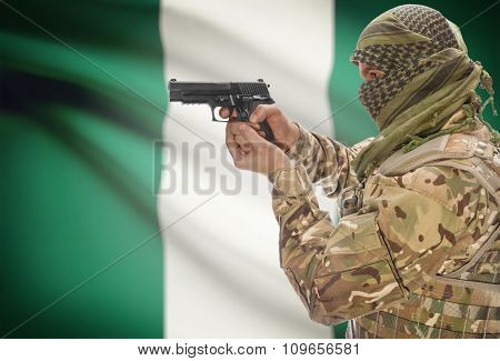 Male With Gun In Hand And National Flag On Background - Nigeria