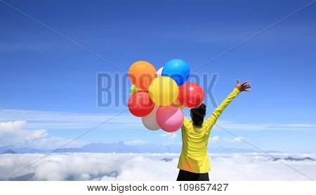 young woman with balloons on mountain peak