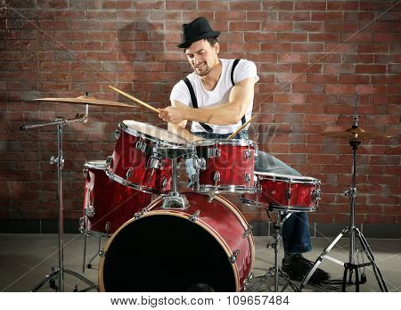 Musician playing the drums on brick wall background