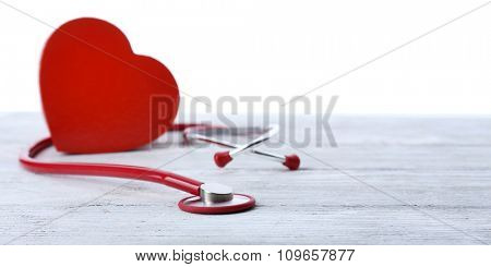 red stethoscope with heart on bright wooden table isolated on white