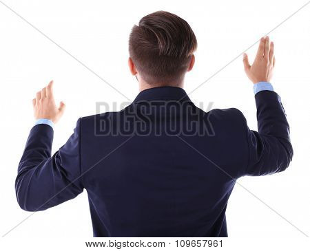 Back view of Caucasian young man in navy blue suit pointing, isolated on white